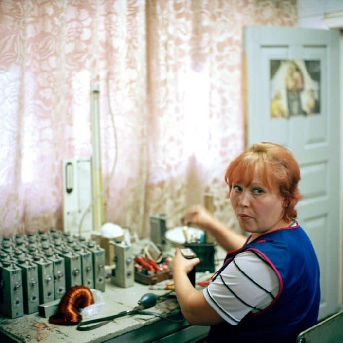 Oekraïne, Vugledar, 06-09-2006 Staats Steen kolenmijn 'Juzshno Donbasskaya Nr 3' (Zuiden van Donbass). Mijnwerkers (Koempels). Een ochtend fotografie op het mijncomplex. Een vrouw repareert de batterijen van de lampen die de mijnwerkers mee ondergronds nemen. Mijnbouw, Steenkool, zwarte goud. PHOTO AND COPYRIGHT ROGER CREMERS