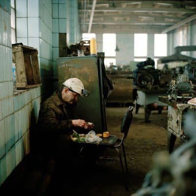 Oekraine, Donetsk, 03-12-2007 De Kujbyshevskaya mijn in het Azotny district in het westen van Donetsk. In en rond de werkplaats waar electrisch gereedschap wordt gerepareerd en waar zwaar metaal ligt opgeslagen. Een arbeider nuttigt zijn lunch. PHOTO AND COPYRIGHT ROGER CREMERS