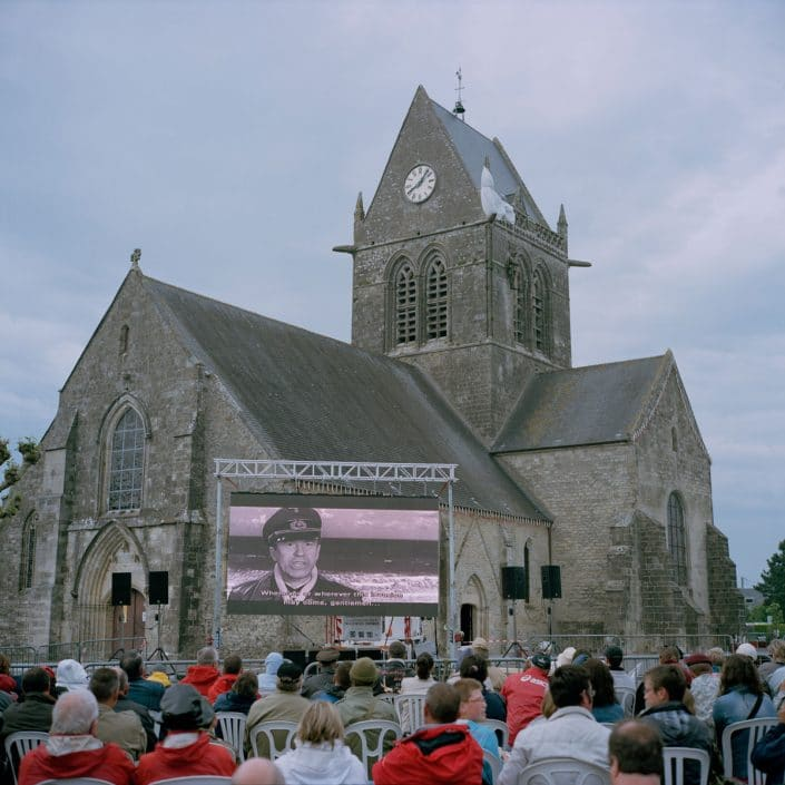 "Frankrijk, Sainte-Mere-Eglise, 02-06-2012 The church in Sainte-Mère-Eglise. People watch the movie ""The Longest Day"" from 1962. For the memory to John Steele who hang during the air landings on 6 June 1944 with his parachute on the churchtower. John Steele survived the raid by playing dead. PHOTO AND COPYRIGHT ROGER CREMERS"