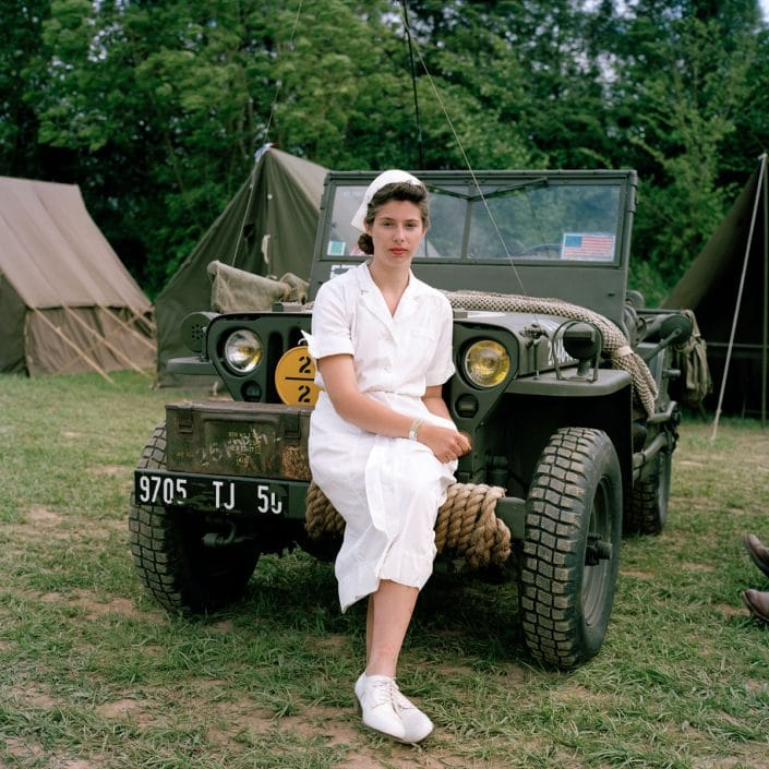 Frankrijk, Carenten, 02-06-2012 Reenactors next to the city centre of Carentan. A lady dressed as a NUrse is sitting on a Jeep. PHOTO AND COPYRIGHT ROGER CREMERS