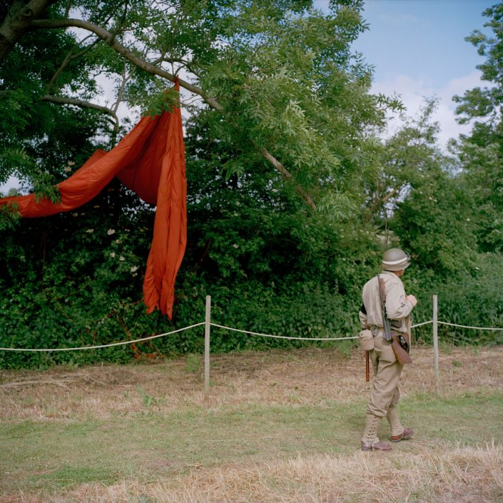 Frankrijk, Carentan, 03-06-2012 A reenactor dressed as a Military Police walks in front of a parachute PHOTO AND COPYRIGHT ROGER CREMERS