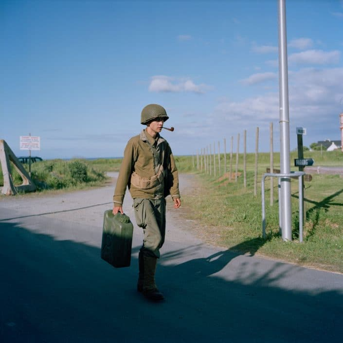 Frankrijk, Vierville-sur-Mer, 03-06-2012 Musée D-Day Omaha at the Route Du Grancamp. A young reenactor with a pipe walks down the road with a Jerry can PHOTO AND COPYRIGHT ROGER CREMERS
