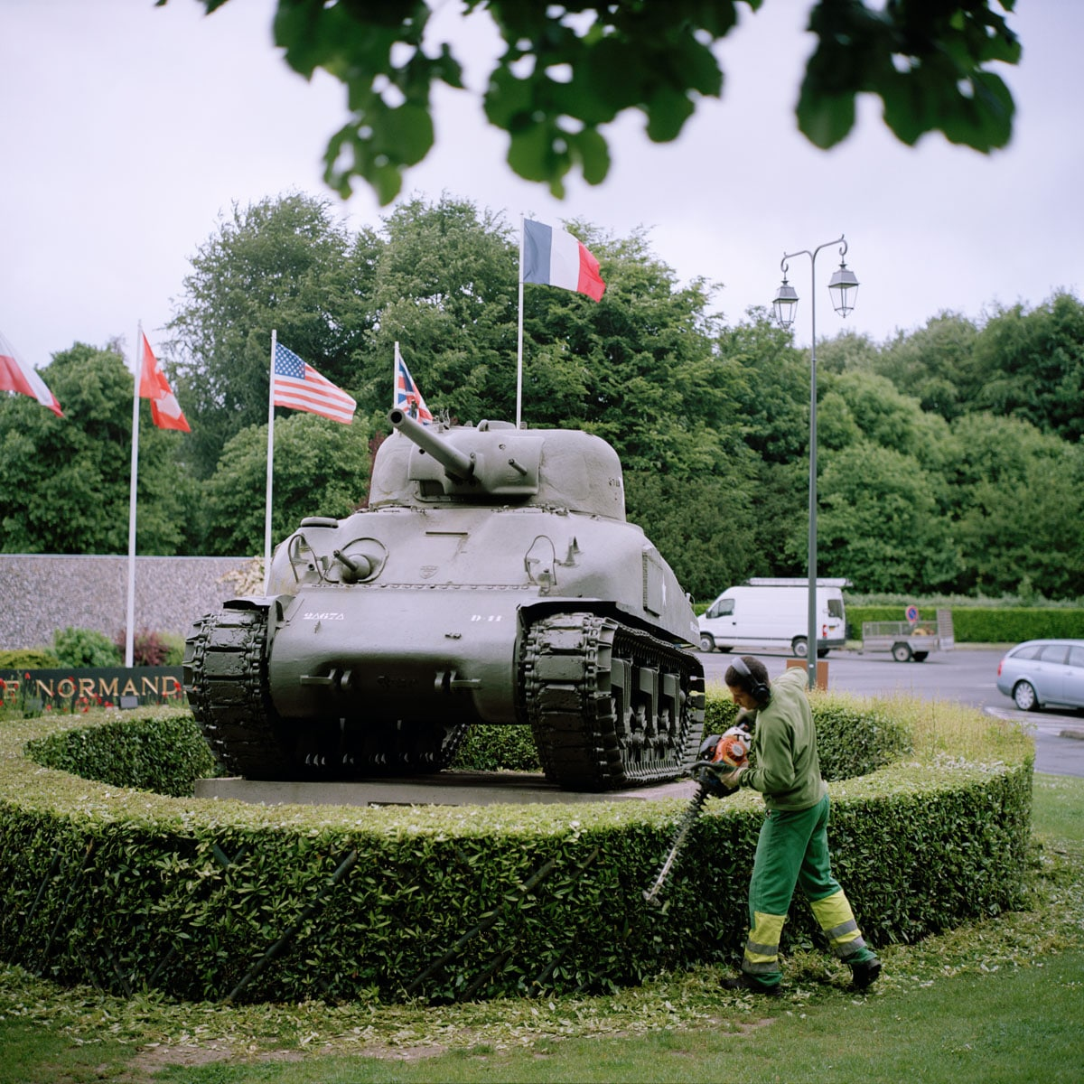 Frankrijk, Bayeux, 04-06-2012 Musée-Mémorial de la Bataille de Normandie. A Gardener in front of a Sherman Tank in front of the museum PHOTO AND COPYRIGHT ROGER CREMERS
