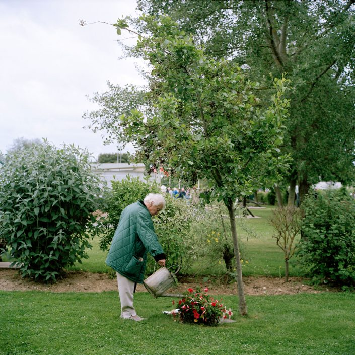 Frankrijk, Ranville, 05-06-2012 Memorial Pegasus A old lady is giving a tree water which is a memorial of a Parachute hero PHOTO AND COPYRIGHT ROGER CREMERS