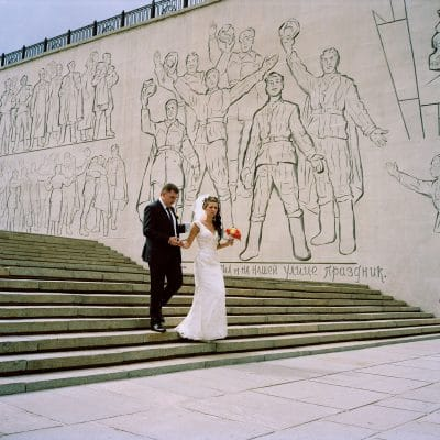 "Russia, Volgograd, 07-09-2013 Mamayev Kurgan memorial complex Two just married people in front of the: The ""Monumental Relief"" is the sixth part of the immens memorial complex on the Mamayev Kurgan (Mamayev Hill). This wall contains scenes of the last phase of the battle of Stalingrad and Soviet soldiers celebrating the victory over the invaders. There is also a symbolic gravestone with the following inscription: ""Here on the 9th of May, 1970, on the day of the Victory of the soviet people over the fascist Germany the capsule, containing a message from the veterans and citizens of the city-hero to the future generations, was buried. It should be opened on the 9th of May, 2045 on the day of 100th jubilee of the victory over the fascist Germany."" PHOTO AND COPYRIGHT ROGER CREMERS"