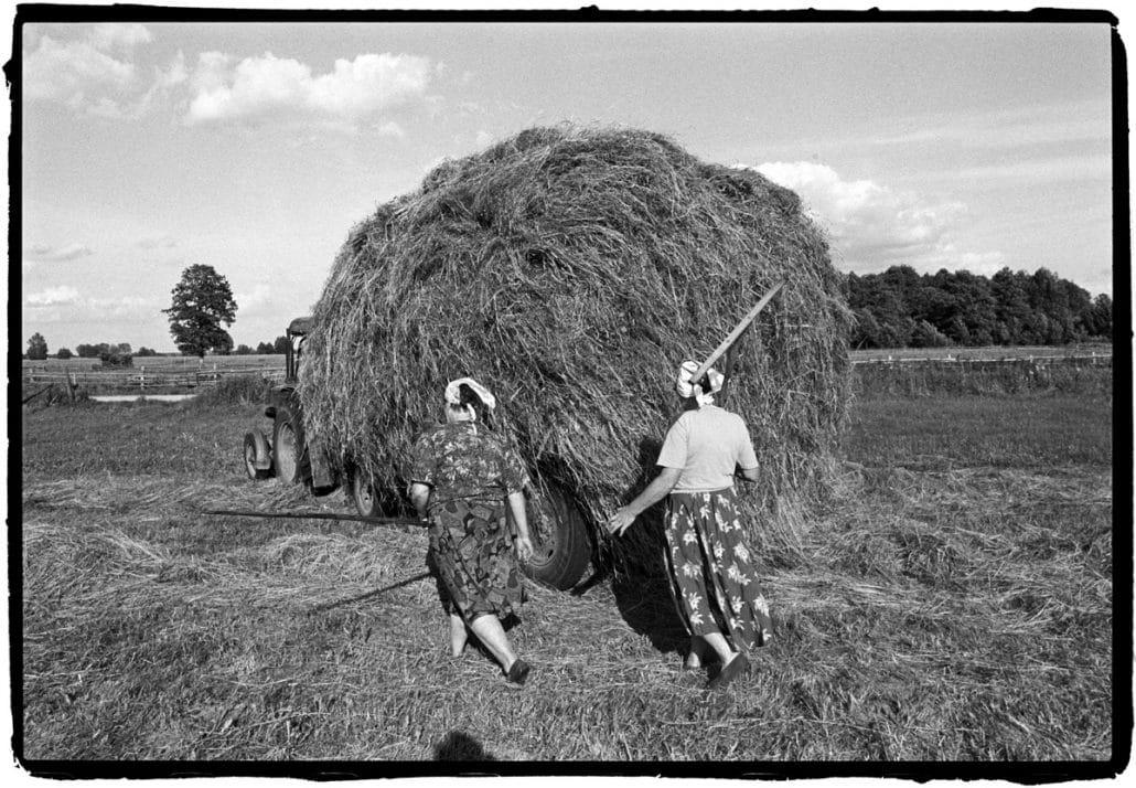 Polen, Woj Podlaskie, 17-06-2002 De familie van Zofia Nos, poolse boeren uit het dorpje Woj Podlaskie. (50 km ten oosten van Bialystok aan de Grens met Wit-Rusland). Twee boerenvrouwen lopen achter de hooiwagen op weg naar de Boerderij. PHOTO AND COPYRIGHT ROGER CREMERS