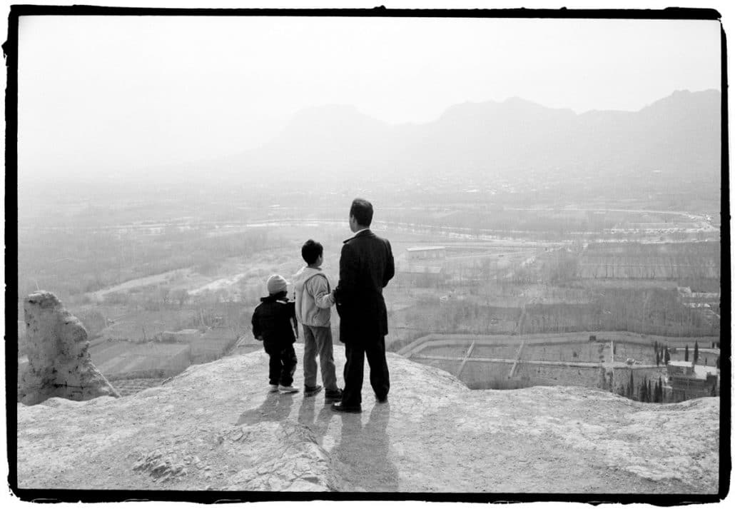 Iran, Esfahan, 08-02-2008 Vader met twee zonen staan aan elkaar gearmd op een ruine heuvel in Esfahan. Zij kijken uit over de rivier en het gebergte aan de overkant. PHOTO AND COPYRIGHT ROGER CREMERS