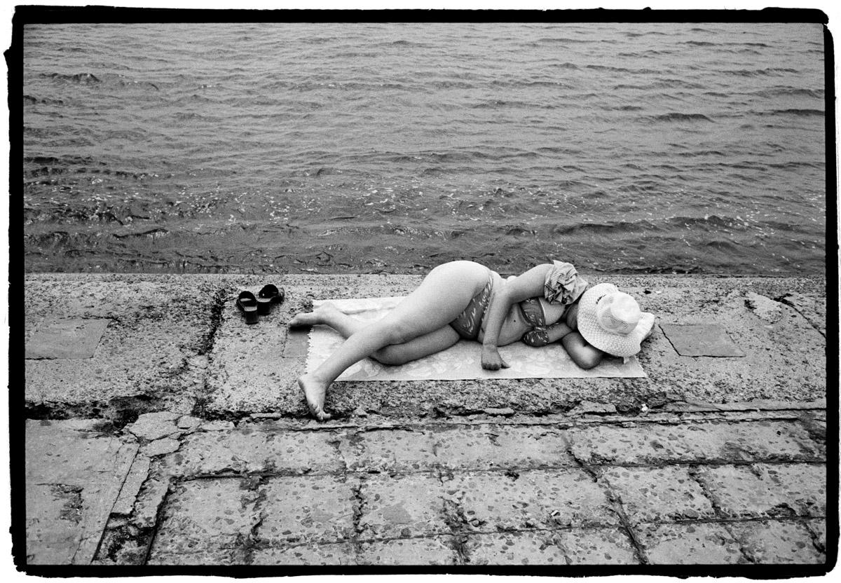 Oekraine, Krim, Eupatoria, 14-06-2008 Yevpatoria is een kustplaats in het westen van de Krim. Deze plaats staat vooral bekend om de vele sanatoria die er gevestigd zijn. Een dikke vrouw ligt te slapen en te zonnenbaden op het betonstrand nabij het oude centrum van de stad. PHOTO AND COPYRIGHT ROGER CREMERS